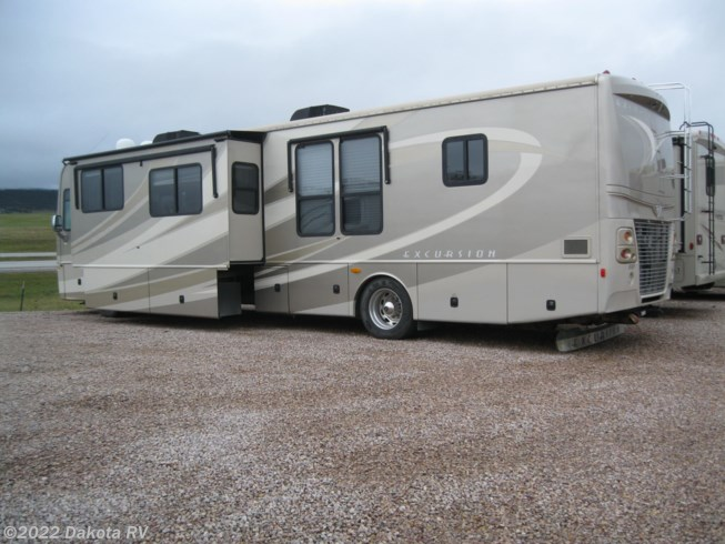 2009 Fleetwood Excursion 40X - Used Diesel Pusher For Sale by Dakota RV in Rapid City, South Dakota features 50 Amp Service, Air Assist Suspension, Air Conditioning, Automatic Leveling Jacks, Auxiliary Battery, Backup Camera, Backup Monitor, Batteries, Battery Charger, Black Tank Flush, Booth Dinette, Cable Prepped, CD Player, Central Vacuum, CO Detector, Convection Microwave, Converter, Corian Countertops, Day/Night Shades, Diamond Shield Paint Protection Film, DVD Player, External Shower, Fantastic Fan, Fiberglass Sidewalls, Fire Extinguisher, Full Body Paint, Furnace, Generator, Glass Shower Door, GPS Navigation, Heat Pump, Hide-A-Bed, Hitch, Icemaker, Inverter, Kitchen Sink, Ladder, Leather Furniture, Leveling Jacks, LP Detector, Medicine Cabinet, Microwave, Non-Smoking Unit, Oven, Pillow Top Mattress, Power Awning, Power Entrance Step, Power Roof Vent, Power Seats, Propane, Queen Bed, Queen Mattress, Recliner(s), Refrigerator, Rocker Recliner(s), Roof Vents, Satellite Dish, Screen Door, Second Roof A/C, Self Contained, Shower, Side View Cameras, Skylight, Slideout, Slide-out Awning, Smoke Detector, Solar Panels, Stove Top Burner, Surround Sound System, Table and Chairs, Tinted Windows, Toilet, TV, TV Antenna, Wardrobe(s), Washer/Dryer Combo, Water Heater