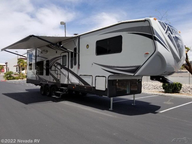 2018 Eclipse Attitude 35 GSG - Used Toy Hauler For Sale by Nevada RV in Las Vegas, Nevada features 50 Amp Service, Air Conditioning, Alloy Wheels, AM/FM/CD, Auxiliary Battery, Awning, Battery Charger, Bluetooth Stereo, CD Player, Ceiling Fan, CO Detector, DVD Player, Fire Extinguisher, Fuel Cell w/ Pump Station, Furnace, Generator, Inverter, King Size Bed, Kitchen Sink, Ladder, LED HDTV, Leveling Jacks, Medicine Cabinet, Microwave, Outside Entertainment Center, Oven, Overhead Cabinetry, Power Awning, Power Stabilizer Jacks, Refrigerator, Removable Table, Rocker Recliner(s), Roof Vents, Shower, Skylight, Slideout, Smoke Detector, Solar Panels, Solid Surface Countertops, Spare Tire Kit, Stabilizer Jacks, Stereo System, Stove Top Burner, Toilet, Water Heater